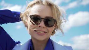 La mujer rubia joven imponentemente hermosa en un vestido blanco y gafas de sol tipo aviador hizo excursionismo por la sol almacen de metraje de vídeo