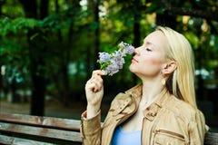 La mujer rubia joven inhala el olor de flores en el parque de la primavera fotografía de archivo libre de regalías