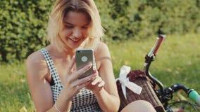 La mujer rubia joven magnífica en un vestido hermoso de moda se sienta en la hierba verde en el parque de la ciudad por la bicicl metrajes