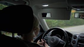 La mujer rubia joven pinta sus labios en el coche almacen de metraje de vídeo