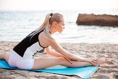 La mujer rubia joven que hace estirar ejercita en la estera de la yoga Imágenes de archivo libres de regalías