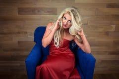 La mujer rubia joven se sienta en la butaca Muchacha hermosa en vestido rojo elegante foto de archivo libre de regalías