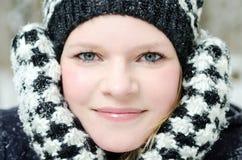 Mujer rubia joven con el retrato de madera del invierno de la gorrita tejida y de la bufanda Foto de archivo libre de regalías