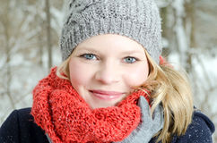Mujer rubia joven con el retrato de madera del invierno de la gorrita tejida y de la bufanda Fotografía de archivo libre de regalías