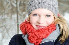 Mujer rubia joven con el retrato de madera del invierno de la gorrita tejida y de la bufanda Foto de archivo