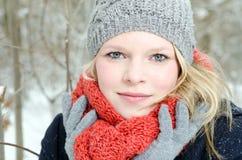 Mujer rubia joven con el retrato de madera del invierno de la gorrita tejida y de la bufanda Fotografía de archivo