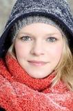 Mujer rubia joven con el retrato de madera del invierno de la gorrita tejida y de la bufanda Imagen de archivo