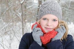 Mujer rubia joven con el retrato de madera del invierno de la gorrita tejida y de la bufanda Fotos de archivo