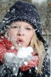 La mujer rubia joven sopla en un puñado de nieve Imágenes de archivo libres de regalías