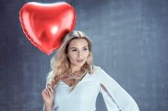 La mujer rubia joven sostiene un globo en forma de corazón Imágenes de archivo libres de regalías