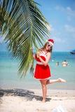 La mujer rubia linda en vestido, gafas de sol y el sombrero rojos de santa se coloca en la palmera en la playa tropical exótica C Fotografía de archivo