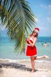 La mujer rubia linda en vestido, gafas de sol y el sombrero rojos de santa se coloca en la palmera en la playa tropical exótica C Imagen de archivo