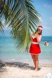 La mujer rubia linda en vestido, gafas de sol y el sombrero rojos de santa se coloca en la palmera en la playa tropical exótica C Fotos de archivo
