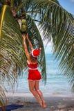 La mujer rubia linda en vestido rojo y el sombrero de santa saltan al coco de las palmeras en la playa tropical exótica Concepto  Fotos de archivo libres de regalías