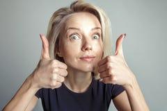 La mujer rubia muestra dos pulgares para arriba foto de archivo