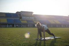 La mujer rubia practica yoga en parque Imagen de archivo