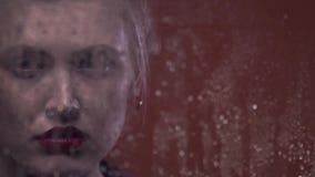La mujer rubia retra con los pendientes rojos está triste, las gotas de lluvia en la ventana, cierre para arriba almacen de metraje de vídeo