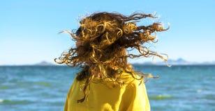 La mujer rubia sacude la cabeza con el pelo rizado en la playa foto de archivo