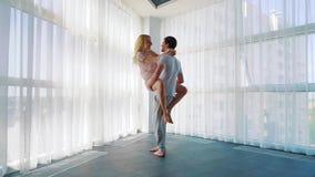 La mujer rubia salta en los brazos del hombre y él hace girar alrededor cerca de ventana francesa almacen de video