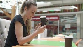 La mujer rubia se está sentando en la tabla en la alameda grande, té de consumición, controles llama por teléfono almacen de metraje de vídeo