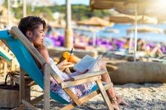 La mujer rubia se relaja en una silla del sol en una playa foto de archivo