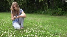 La mujer rubia se sienta en corona de la cabeza de la armadura del prado de las flores de la planta del trébol 4K almacen de video