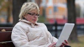 La mujer rubia se sienta en el banco cerca del camino y utiliza la tableta almacen de metraje de vídeo