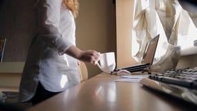 La mujer rubia se sienta en la tabla, pone la taza al lado de ella en gabinete en casa almacen de video