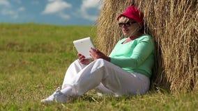 La mujer rubia se sienta en una hierba verde cerca de pajar y comunica vía la tableta metrajes