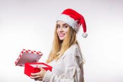 La mujer rubia sonriente alegre alegre en un sombrero y un suéter rojos de Papá Noel abrió su regalo del Año Nuevo, una caja y mi foto de archivo