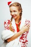La mujer rubia sonriente bastante feliz de los jóvenes en la Navidad en el sombrero rojo y el día de fiesta de santas adornó la t Imagen de archivo libre de regalías