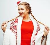 La mujer rubia sonriente bastante feliz de los jóvenes en la Navidad en el sombrero rojo y el día de fiesta de santas adornó la t Foto de archivo
