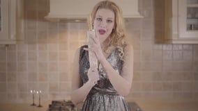 La mujer rubia sonriente joven del retrato con la barra de labios roja y los pechos grandes en vestido negro frota el rodillo con almacen de video
