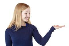 La mujer rubia sostiene la palma con el espacio del anuncio Imagen de archivo