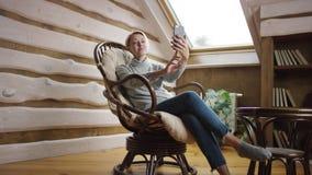 La mujer rubia toma el selfie en el ático almacen de video