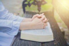La mujer ruega con la biblia en el jardín Imagenes de archivo