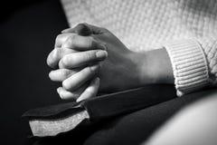 La mujer ruega con las manos dobladas en la biblia Foto de archivo libre de regalías