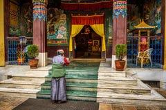 La mujer ruega delante de un templo budista Imagenes de archivo