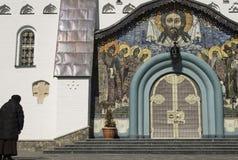 La mujer ruega en la entrada a la iglesia Fotos de archivo libres de regalías