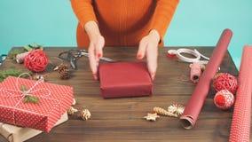 La mujer s da el embalaje del regalo de la Navidad en fondo de madera oscuro almacen de video