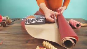 La mujer s da el embalaje del regalo de la Navidad en fondo de madera oscuro almacen de metraje de vídeo