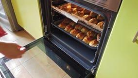La mujer saca la bandeja con muchos pasteles cocidos deliciosos tradicionales del horno caliente en panadería almacen de video