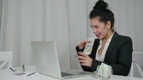 La mujer saca de dólares de EE. UU. su ordenador portátil y guiña concepto de abundancia almacen de video