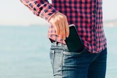 La mujer saca el teléfono de su bolsillo en la playa Fotos de archivo libres de regalías