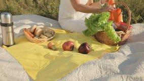 La mujer saca la fruta y bebe de la cesta y los pone al lado de otra cesta con diversos rollos