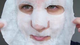 La mujer saca su máscara de los cosméticos y mira la cámara con una sonrisa Antienvejecedor y cosm?ticos para el tratamiento almacen de video