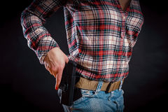 La mujer saca una pistola de la pistolera foto de archivo libre de regalías