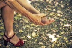 la mujer saca una sandalia Foto de archivo