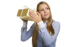 La mujer sacude el presente y el intento para descubrir cuál está dentro Foto de archivo libre de regalías