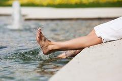 La mujer salpica con los pies en el agua Fotos de archivo